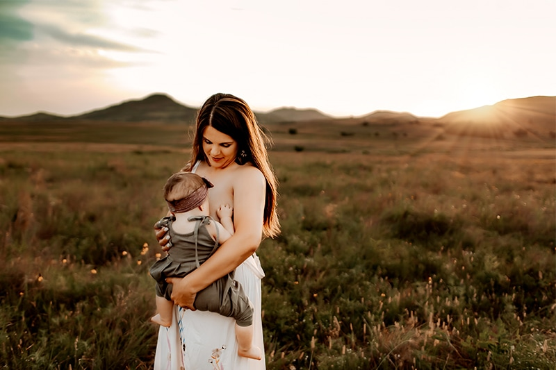 Newborn Photography, a young mother holds her baby and gazes at her as she walks through a grassy meadow